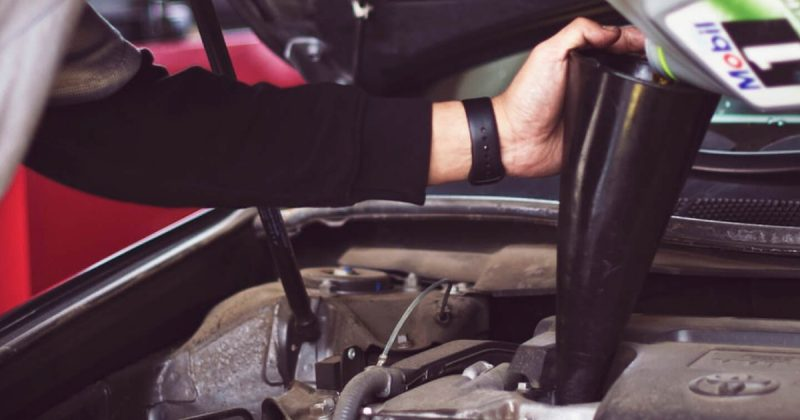 Mechanic changing oil in car engine