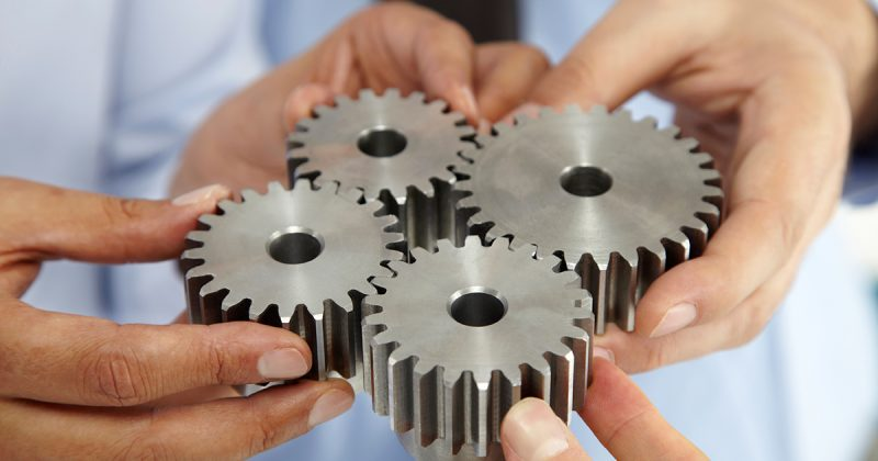 Close up of hands holding gears